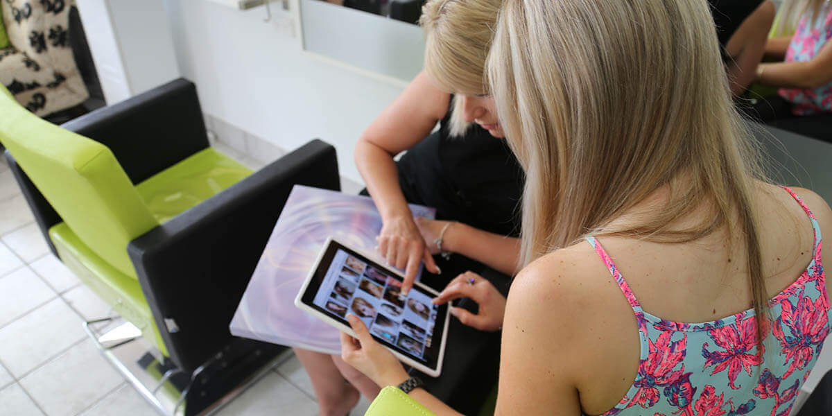 Samantha Jones Hair Co Our Work Image Gallery - Blonde Hair Salon Client Looking at Hair Photo Images on Tablet